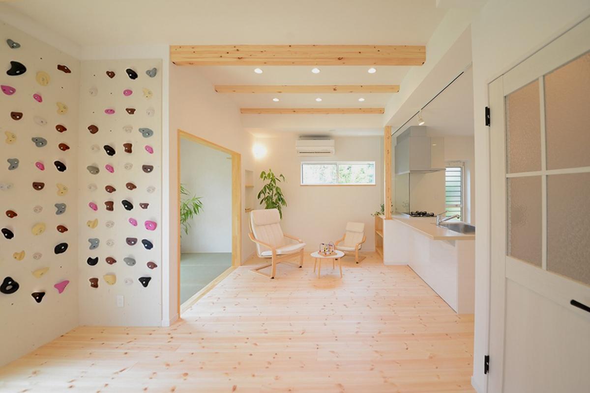 真っ白い壁にボルダリングのアクセント。無垢材の床と梁と琉球畳で、シンプルで爽やかなLDKができあがりました。キャンバス地の親子チェアでくつろぎます。