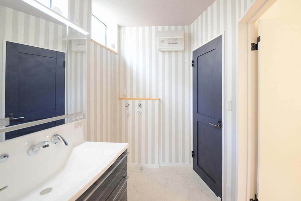 キッチンと隣接する水まわり空間は、ネイビーのドアにストライプの壁紙。アリスが住んでいそうな可愛らしい空間での家事は気持ちが上がります。