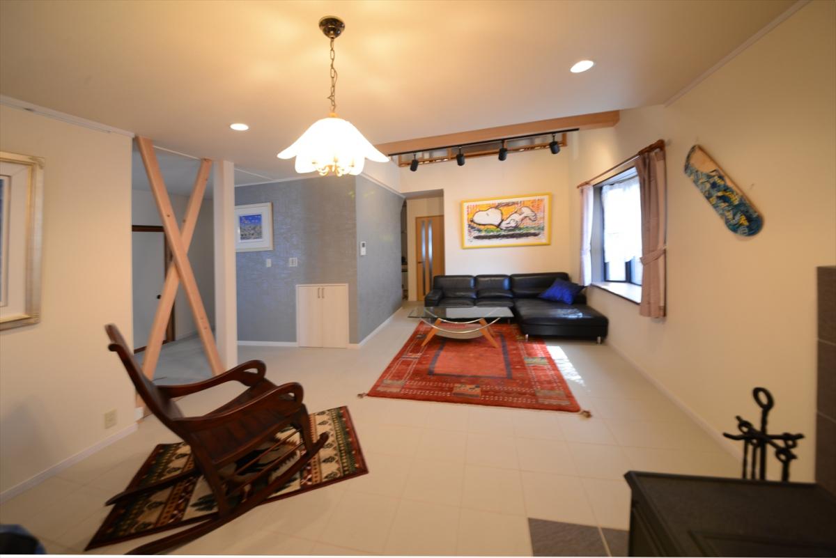 元々の1階リビングダイニングは、趣味の絵画を楽しむギャラリー空間に変身。薪ストーブと白いタイルの床がお気に入りの絵画を引き立てます。